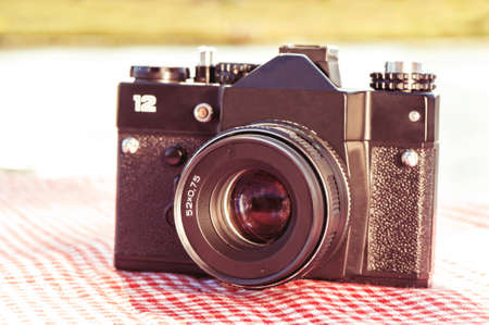 photocamera: Filtered shot of an old square retro photocamera. Outdoors close-up.