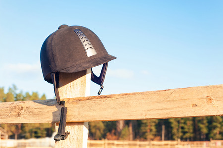 Equestrian equipment - helmet  hanging on the wooden fence with blue sky background. Outdoors close-up. photo