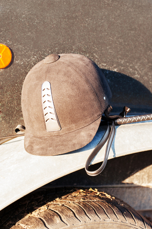 fender: Equestrian helmet forgotten on horse trailers fender. Outdoors.
