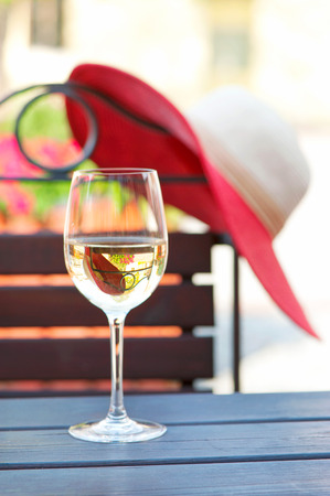 arranging chairs: Glass of delicious white wine on wooden table in summer restaurant. Outdoors.