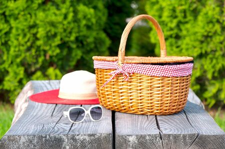 Ready for summer weekend. White sunglasses summer hat and wicker basket on wooden table. Summer park outdoors.