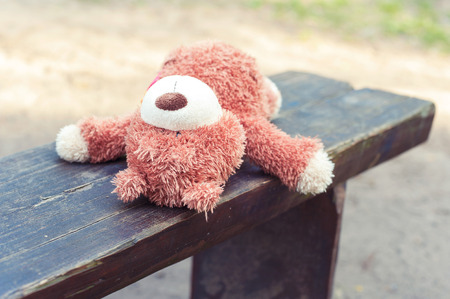 sorrowfully: Abandoned on the wooden bench lonely teddy bear toy. Awaiting for owner. Outdoors.
