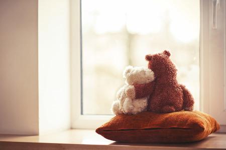 Two embracing teddy bears looking through the window sitting on window-sill. Archivio Fotografico