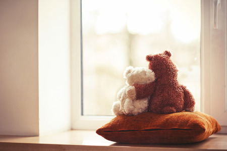 Two embracing teddy bears looking through the window sitting on window-sill. Stock Photo