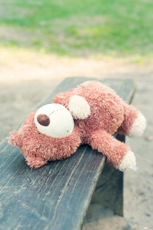 sorrowfully: Lonely abandoned teddy bear toy lying on the wooden bench. Awaiting for owner. Outdoors. Stock Photo