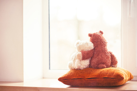 Two embracing teddy bear toys  looking through the window sitting on window-sill. Filtered image. Indoors