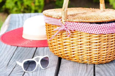 Bereit für den Sommer Wochenende. Weiß Sonnenbrille Sommer Hut und Weidenkorb auf Holztisch im Freien. Standard-Bild - 36160521