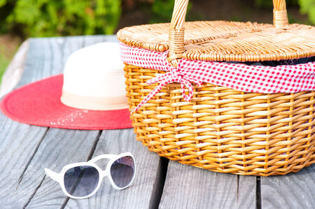 wicker basket: Ready for summer weekend. White sunglasses summer hat and wicker basket on wooden table outdoors.
