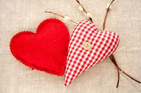 Homemade sewed couple red cotton love heart with spring willow twig. Indoor closeup. photo