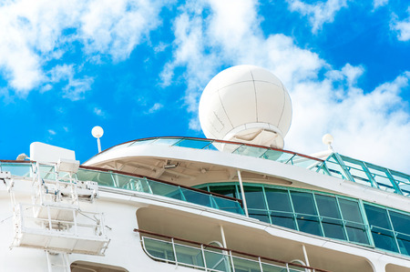 superstructure: Radar, safety and navigation equipment on passenger ship. Cloudy blue sky background.