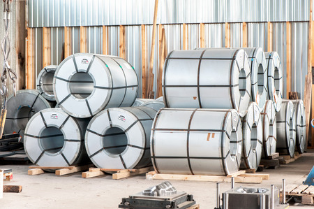 Many bended metal sheet rolls in factory warehouse. Metal engineering. Indoors.