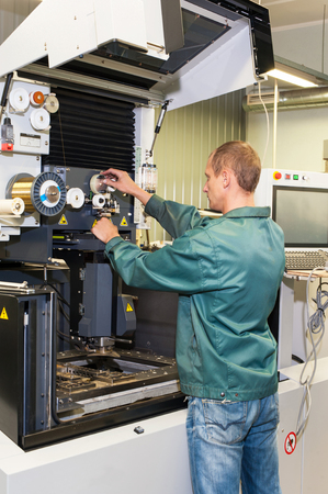 setup operator: Worker- repairman operating industrial cnc machine in workshop. Metalworking and engineering industry, lathe , cnc and milling technology.