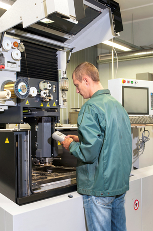 pult: Worker- repairman operating industrial cnc machine in workshop. Metalworking and engineering industry, lathe , cnc and milling technology.