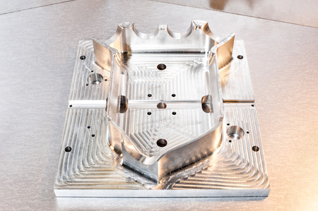 mounting holes: Industrial metal mold blank. Metalworking. CNC milling technology. Mechanical engineering. Indoors closeup.