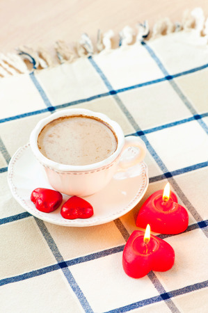 compliment: Valentines day cup of coffee with pair of heart shaped sweet chocolates and candles. Celebration surprise.