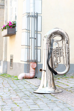 upturned: Big shiny base trumpet standing upturned on the street of old town. Outdoors.