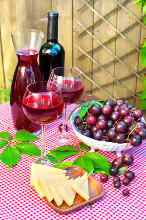 semisweet: Two glasses of delicious homemade semisweet red wine with grapes and cheese. Outdoors still-life. Stock Photo