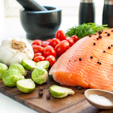 eating fish: Big piece of fresh raw salmontrout with vegetables and seasoning on wooden cutting board- ready to eat, ready to cook. Indoors square close-up image Stock Photo