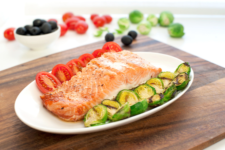 food preparation: Piece of roasted salmon fillet with grilled brussels cabbage and tomatoes. Indoors still-life.