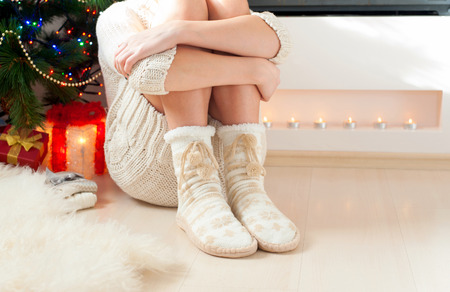 hugging legs: Young girl arms hugging legs in cozy warm woolen ornamental socks with pompons. Indoors. Stock Photo