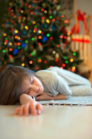 newyear: Little girl sleeping near illuminated new-year tree dreaming about christmas miracles.
