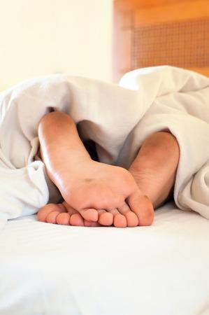 pieds sales: Sleeping petits enfants pieds sales drôles sur des draps blancs. Gros plan intérieur. Banque d'images
