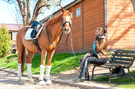 Woman riding trainer near chestnut horse speaking on cell phone. Multicolored outdoors image. Archivio Fotografico