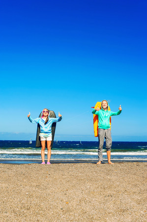 boogie: Two happy smiling girls with boogie boards standing on windy beach showing thumb up - ok sign. Blue sky background. Multicolored summertime outdoors image.