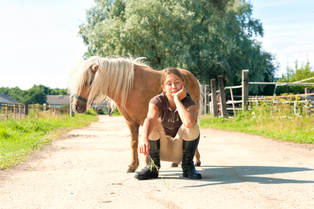 Best friends. Young teenage girl sitting near cute little shetland pony. Summertime outdoors image.