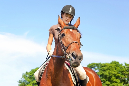 Teenage girl equestrian riding horseback. Vibrant summertime outdoors horizontal image. Stock Photo