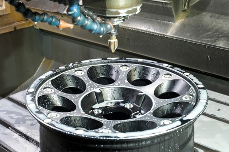 chrome base: Car alloy black new rim die mounting in milling and lathe cnc machine. Angle view of working process. Mechanical engineering and metalworking industry. Indoors image.
