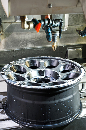 chrome base: Metal car alloy black new rim die mounting in milling and lathe cnc machine. Angle view of working process. Mechanical engineering and metalworking industry. Indoors image.