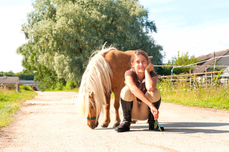 Friendship and trusting. Cheerful teenage girl sitting near cute little shetland pony. Summertime outdoors image.