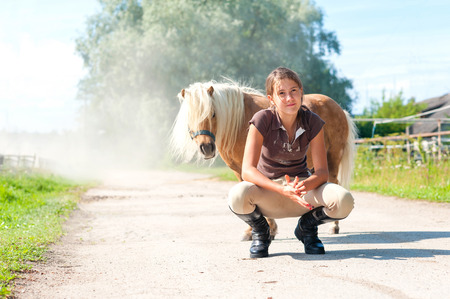trusting: Friendship and trusting. Smiling teenage girl sitting near cute little shetland pony. Summertime outdoors image.