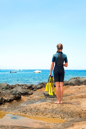 paddles: Young lady in diving suit with paddles standing on Atlantic ocean rock coast. Tenerife, Canary islands, Spain. Vibrant multicolored summertime vertical outdoors image.