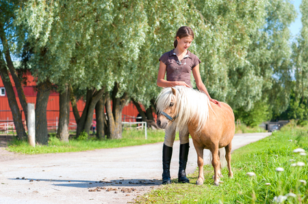 trusting: Friendship and trusting. Smiling teenage girl standing and stroking cute little shetland pony. Summertime outdoors image. Stock Photo