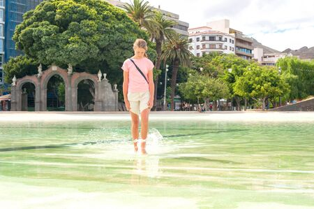 little girl barefoot: Hot summer in the city. Teenage barefoot young girl walking in water of city pool. Plaza de Espana Santa Cruz Tenerife. Filtered multicolored summertime outdoors image. Stock Photo