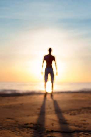 power of thinking: Looking into the future. Ethereal defocused blurred man silhouette standing in sunbeam. Multicolored vibrant summertime outdoors image. Low point of view.