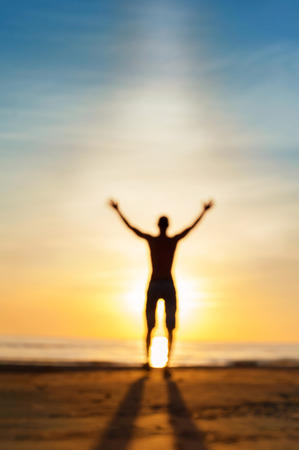 Dialog with heaven. Defocused blurred man phantom silhouette standing in rays of sunlight with raised up arms. Multicolored vibrant summertime outdoors image. Low point of view. Stock Photo