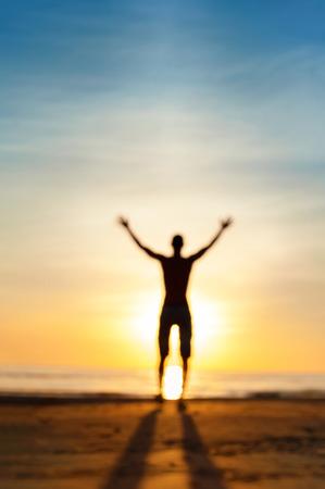 corpo umano: Guardando per la risposta. Sfocato offuscata uomo fantasma silhouette in piedi in raggi del sole con le braccia sollevate. Multicolore vibrante estate outdoors. Basso punto di vista.