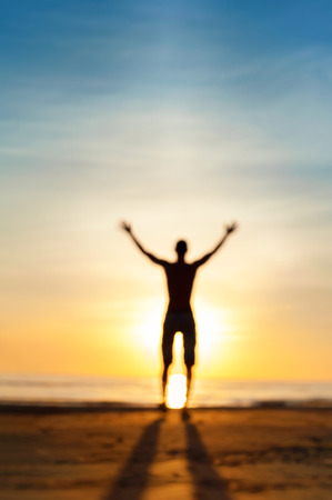 Looking for the answer. Defocused blurred man phantom silhouette standing in rays of sunlight with raised up arms. Multicolored vibrant summertime outdoors image. Low point of view.
