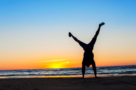 Young sporty man making handstand on the beach. Multicolored sunset background. Horizontal summertime outdoors image. Archivio Fotografico