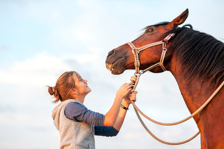 horses: Young cheerful teenage girl calming big spirit chestnut horse. Vibrant multicolored summertime outdoors horizontal image. Stock Photo