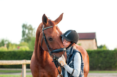 schooling: Young teenage girl equestrian kissing her chestnut horse. Multicolored outdoors horizontal image.