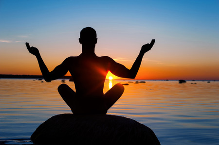 Meditating man silhouette on vibrant sunset background. Multicolored summertime horizontal outdoors image. View from backside.