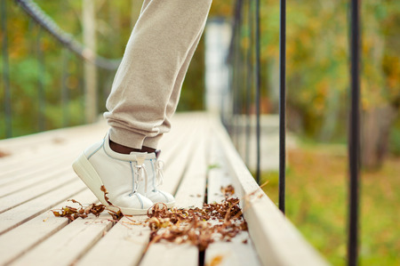 foot bridge: Woman feet in white shoes standing tiptoe on hanging bridge in autumn park. Side view. Outdoors fall season multicolored horizontal image.