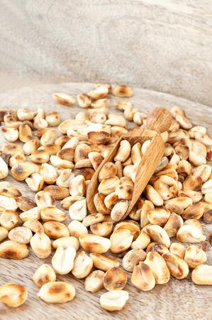 goober peas: Heap of roasted peeled dry peanuts on wooden plank. Indoors closeup vertical image.