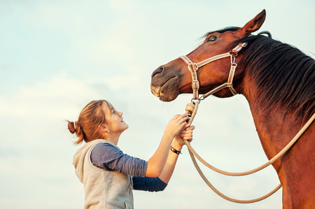 Young cheerful teenage girl calming big spirit chestnut horse. Vibrant multicolored summertime outdoors horizontal image with filter. Stock Photo