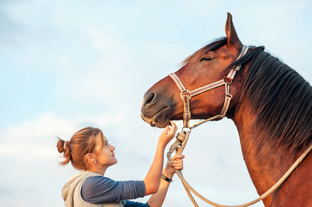 horse harness: Young cheerful teenage girl stroking big chestnut horses nose. Vibrant multicolored summertime outdoors horizontal image with filter Stock Photo