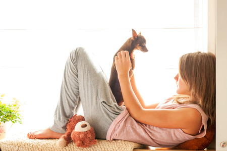 toyterrier: Good morning! Young girl in pyjamas holding her lovely Toy-terrier dog in rays of sunlight. Multicolored vibrant horizontal indoors image.
